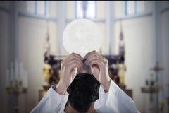 De predikanthand heft een kerkgemeenschapbrood in kerk op stock foto