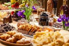 De premiecognac van close-updegustation en snacks, verse en droge vruchten, de kaas van de stukkenparmezaanse kaas, honingraten,  stock foto