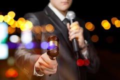 De presentator met een microfoon in zijn hand houdt een veiling royalty-vrije stock fotografie
