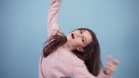 De pret, mooi tienermeisje in heldere sweater, het voor de gek houden, die camera bekijken, blaast wangen op, over pastelkleurbla stock footage