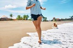 De pret van het de zomerstrand Vrouw die met hond loopt Vakantievakanties De zomer Stock Foto
