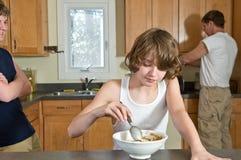 De pret van het familieontbijt - tienerbroers die graangewas hebben: spontane schoten royalty-vrije stock afbeeldingen