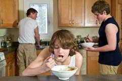 De pret van het familieontbijt - tienerbroers die graangewas hebben: spontane schoten stock afbeeldingen