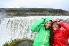 De pret van het reispaar door Dettifoss waterval, IJsland stock fotografie