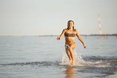 De pret van het water de meisjeslooppas langs de kust royalty-vrije stock fotografie