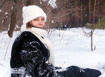 De pret van de winter Het jonge meisje situeert in sneeuw en bekijkt camera Stock Foto