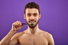 De prettige glimlachende mens gaat zijn tanden borstelen royalty-vrije stock foto's