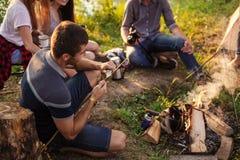 De prettige mens snijdt een houten stok met mes voor de jacht stock foto