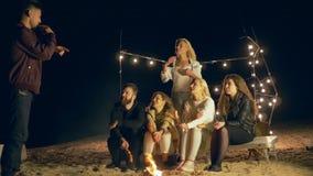 De pretvakantie, vriendschappelijk bedrijf speelt in grappige spelen door vuur in zand op dijk stock videobeelden