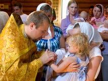 De priester houdt de rite van het insmeren van het kind na doopsel royalty-vrije stock foto's
