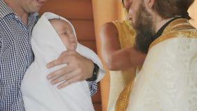 De priester kleedt een handdoek op weinig baby na een ceremonie van doopsel in wijwater stock videobeelden