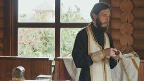 De priester treft voor de rite van doopsel in kerk voorbereidingen stock videobeelden