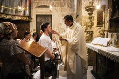 De priester van de Kerk van Heilig Grafgewelf geeft heilige kerkgemeenschap aan de gelovige mens met andere gelovigen die op hun  stock foto