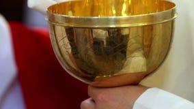 De priester verdeelt Heilige Communie tijdens massa stock videobeelden
