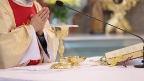 De priester viert een massa en een heilige kerkgemeenschap bij de kerk stock video