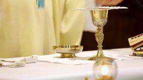 De priester viert een massa en een heilige kerkgemeenschap bij de kerk stock footage