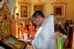 De priester voert de rite van doopsel van kind in Oekraïense kerk uit Royalty-vrije Stock Afbeeldingen