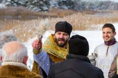 De priester zegent parochianen Stock Foto