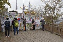De prikkeldraadomheining scheidt Zuiden van Noord-Korea - Zuidkoreaanse vlaggen en gebedwensen in bijlage aan omheining voor gesc Stock Fotografie