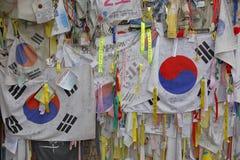 De prikkeldraadomheining scheidt Zuiden van Noord-Korea - Zuidkoreaanse vlaggen en gebedwensen in bijlage aan omheining voor gesc Royalty-vrije Stock Afbeelding