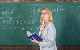 De principes kunnen het onderwijs efficiënt maken Het vrouwenonderwijs dichtbij bord in klaslokaal Het efficiënte onderwijs impli royalty-vrije stock afbeeldingen