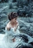 De prinses zit op de grond in het bos, onder de varen en het mos Een ongebruikelijk gezicht Op de dame is een witte wijnoogst Stock Afbeelding