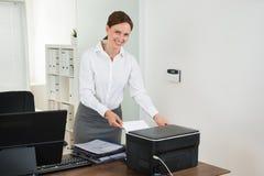 De Printer van secretaresseinserting paper in Royalty-vrije Stock Afbeelding