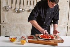 De privé chef-kok die van het restauranthotel pizza voorbereiden die bovenste laagjes toevoegen stock fotografie