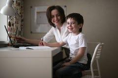 De privé-leraar onderwijst kleuter met laptop, echt huis royalty-vrije stock afbeeldingen
