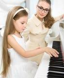 De privé-leraar onderwijst weinig pianist om piano te spelen stock fotografie