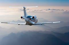 De privé straal, het passagiers wide-body vliegtuig of het vliegtuig vliegen in de blauwe hemel over de wolken en de bergen De zo Royalty-vrije Stock Afbeeldingen