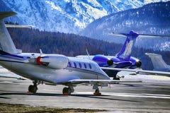 De privé stralen, de vliegtuigen en de helikopters in de mooie sneeuw behandelden bergen van alpen in St Moritz Switzerland Stock Foto