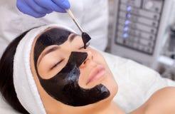 De procedure om een zwart masker op het gezicht van een mooie vrouw toe te passen stock fotografie