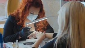 De procedure om spijkers te schilderen Manicureprocedure in de schoonheidssalon Stock Afbeelding