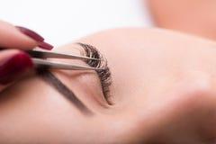 De procedure van de wimperuitbreiding bij schoonheidssalon stock fotografie