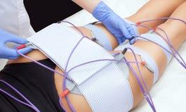 De procedure van myostimulation op de benen en de billen van een vrouw in een schoonheidssalon stock foto's