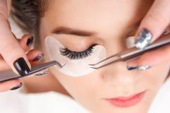 De Procedure van de wimperuitbreiding Het oog van de vrouw met lange wimpers Sluit omhoog, selectieve nadruk stock afbeelding