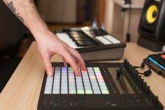 De producent maakt een muziek op professioneel productiecontrolemechanisme met drukknopstootkussens stock foto's