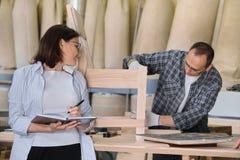 De productie van de meubilairschrijnwerkerij, werkende mannelijke schrijnwerker en vrouwelijke bedrijfseigenaar met notitieboekje royalty-vrije stock foto's