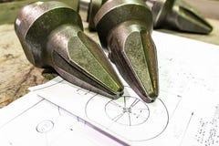 De productie van snijders voor ontvezelmachines ligt op de tekening, het scherpe hulpmiddel om toestellen, toestellen op een male royalty-vrije stock afbeeldingen