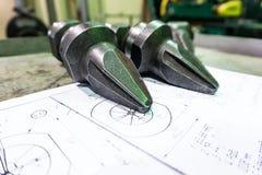 De productie van snijders voor ontvezelmachines ligt op de tekening, het scherpe hulpmiddel om toestellen, toestellen op een male royalty-vrije stock foto