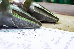 De productie van snijders voor ontvezelmachines ligt op de tekening, het scherpe hulpmiddel om toestellen, toestellen op een male stock fotografie