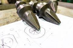 De productie van snijders voor ontvezelmachines ligt op de tekening, het scherpe hulpmiddel om toestellen, toestellen op een male stock foto's