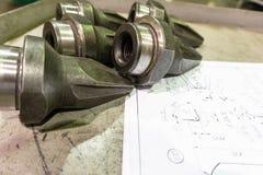 De productie van snijders voor ontvezelmachines ligt op de tekening, het scherpe hulpmiddel om toestellen, toestellen op een male stock foto