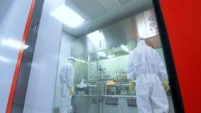 De productieproces van de twee farmaceutisch arbeiderscontrole Wetenschappers in laboratorium stock footage