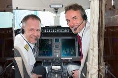 De proefbemanning die van de vliegtuigcockpit bij camera glimlachen Royalty-vrije Stock Afbeeldingen