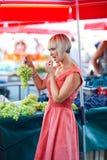 De proevende druiven van de vrouw in markt Royalty-vrije Stock Foto
