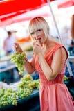 De proevende druiven van de vrouw in markt Stock Afbeeldingen