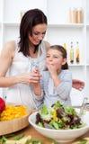 De proevende salade van het meisje met haar moeder stock afbeeldingen