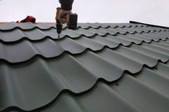 De professionele arbeiderswerken aangaande installatie van een dak van een dak door bladen van een metaal betegelen en boren een  royalty-vrije stock afbeeldingen